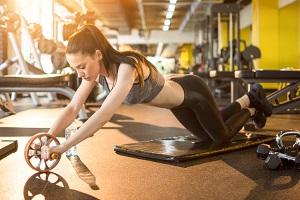 Tjej som använder maghjul på gym för bra träning i core och mage.