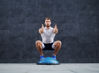 Kille som gör övningar på en halv balansboll.