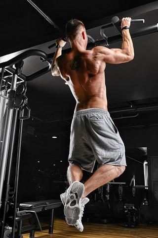Kille som tränar på olika övningar med chinstång.