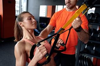 Tjej som tränar med band och övar på bicepscurls.