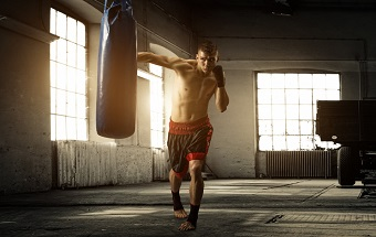 Man som boxar boxsäck hemma.
