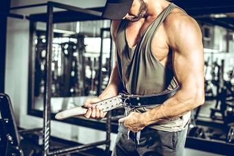 Tar på sitt lyftarbälte för att träna marklyft med fria vikter.