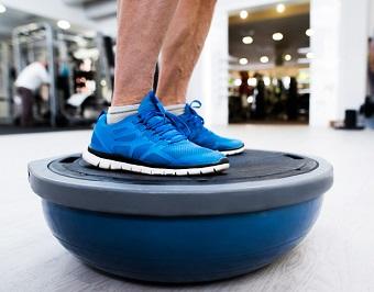 Man som använder en bosuboll för balansen på gymmet.