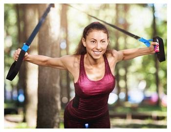 Tjej som tränar utomhus med träningsband som träningsredskap.