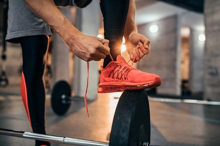 Kille som knyter tyngdlyftarskor på gym innan knäböj.